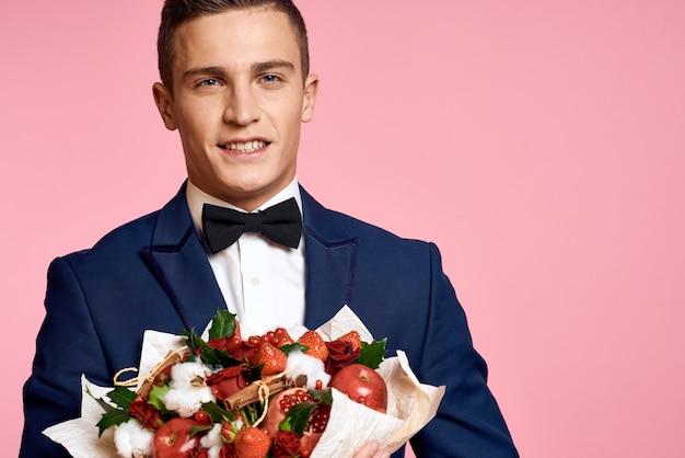 Красивый мужчина в классическом костюме с букетом цветов