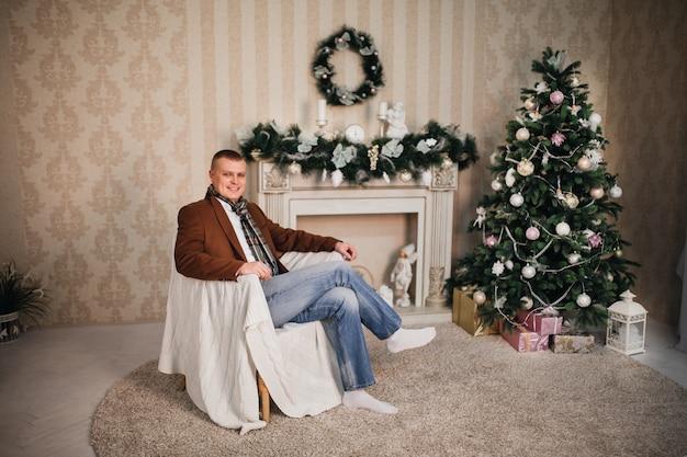 椅子に座っているコートとスカーフのハンサムな男