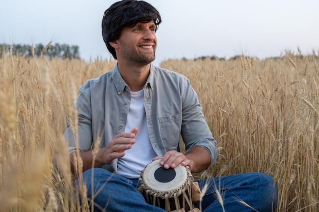 회색 셔츠를 입은 잘생긴 남자가 밀밭에 앉아서 드럼을 치고 있다