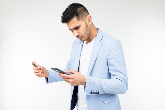 Красивый мужчина в куртке заказывает покупки через интернет со смартфона, держа в руках кредитную карту.
