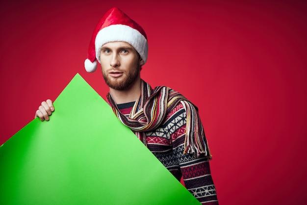 バナーの休日の赤い背景を保持しているサンタ帽子のハンサムな男。高品質の写真