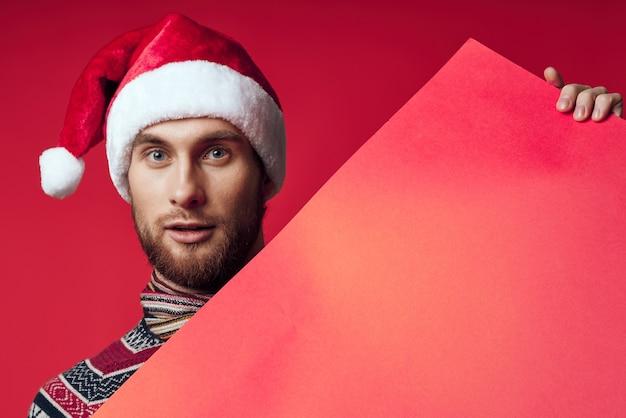バナーの休日の赤い背景を保持しているサンタ帽子のハンサムな男