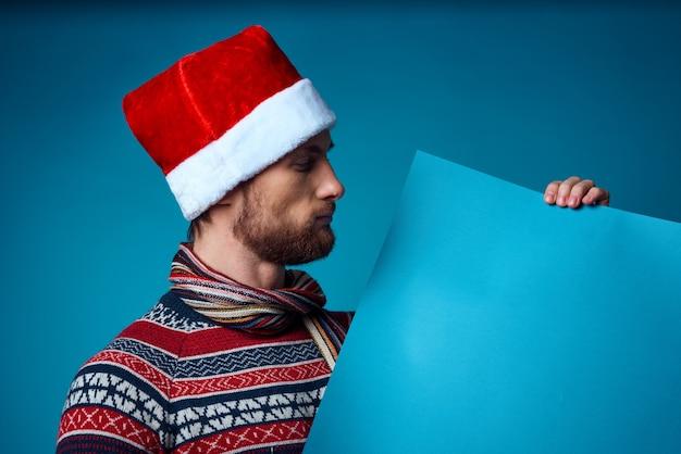 バナーホリデースタジオポーズを保持しているサンタ帽子のハンサムな男