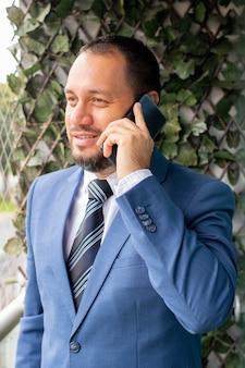 スーツとネクタイでハンサムな男は電話で話しています。