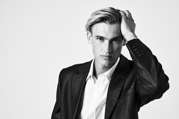 スーツを着たハンサムな男が彼の顔の近くに手を握ってファッショナブルな髪型の黒と白の写真