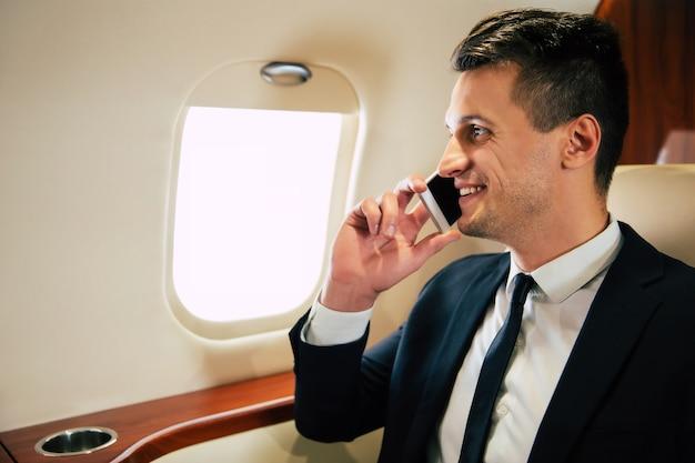 スーツを着たハンサムな男が笑顔で窓越しに電話で話し、ラップトップとコーヒーを片手にビジネスクラスを飛んでいます。