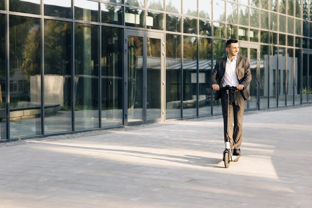 Красивый мужчина в костюме, езда на электросамокате в городе, взрослый бизнесмен, езда с электрическим