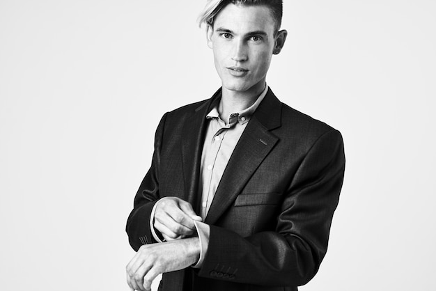 Красивый мужчина в костюме самоуверенно поправляет рукав