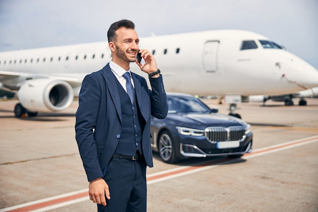飛行機の前に立って電話で話しているスーツを着たハンサムな男