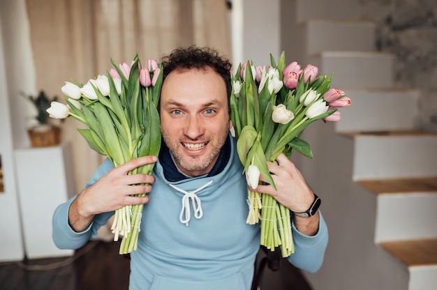 スウェットシャツを着たハンサムな男は笑顔でチューリップの花束を手に持っています