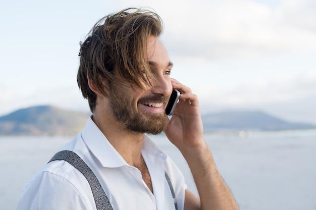 ビーチで電話での会話のハンサムな男