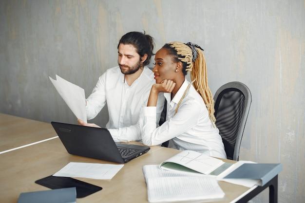 흰 셔츠에 잘 생긴 남자입니다. 파트너와 함께 아프리카 여자입니다. 노트북을 가진 남자.