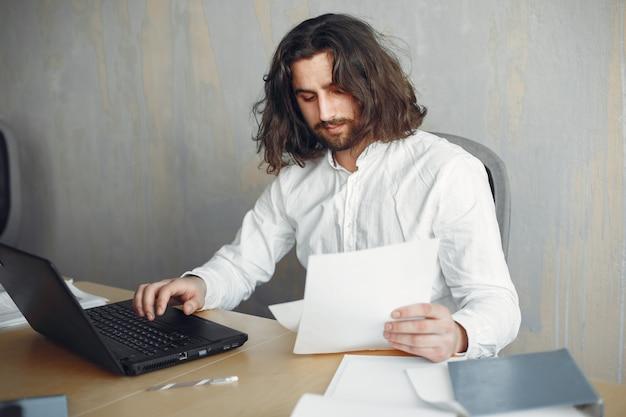 흰 셔츠에 잘 생긴 남자입니다. 사무실에서 일하는 사업가. 노트북을 가진 남자.