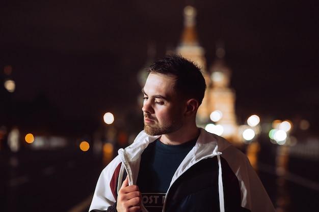ウインドブレーカーのハンサムな男が赤の広場で一晩ポーズします。