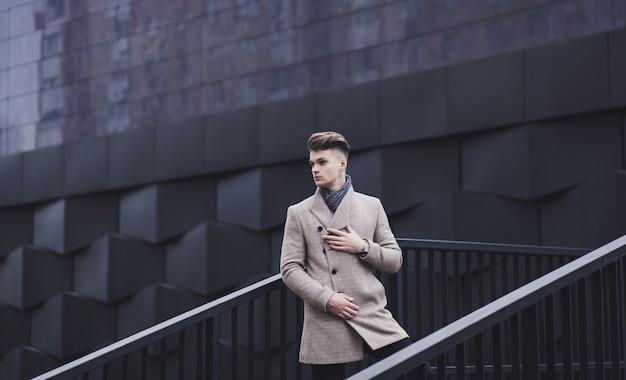 都市環境の秋のコートでハンサムな男