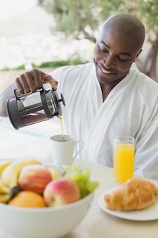 Красивый мужчина в халате с завтраком на улице