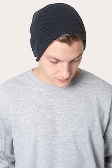 Красивый мужчина в черной шапке и сером свитере зимней одежды студии съемки