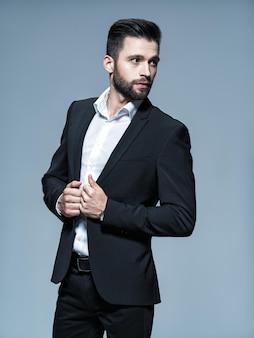 Красивый мужчина в черном костюме с белой рубашкой - позирует привлекательный парень с модной прической. уверенный в себе мужчина с короткой бородой. взрослый мальчик с каштановыми волосами. полный портрет.