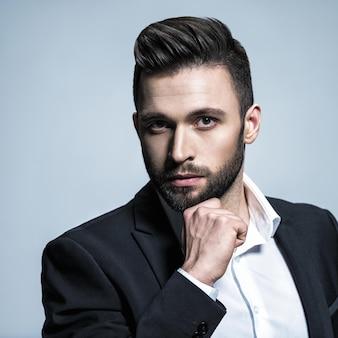 白いシャツと黒のスーツを着たハンサムな男-ファッションの髪型を持つ魅力的な男をポーズします。短いあごひげを持つ自信のある男。茶色の髪の大人の男の子。