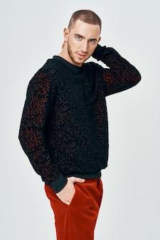 黒のセーターのハンサムな男ポーズファッション服スタジオ