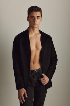 Красивый мужчина в черной расстегнутой куртке привлекательно смотрится роскошными студийными моделями. фото высокого качества