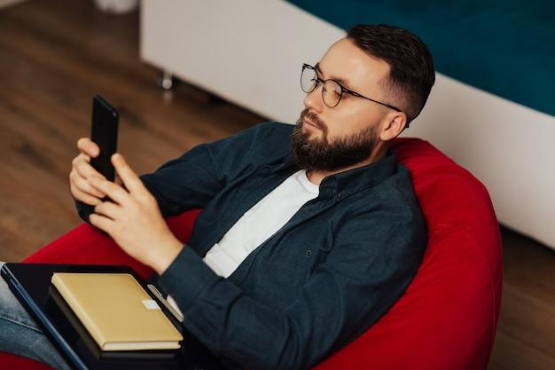 青いシャツと眼鏡をかけたハンサムな男が肘掛け椅子に座って、携帯電話を手に、ラップトップとノートブックを膝に抱えています。