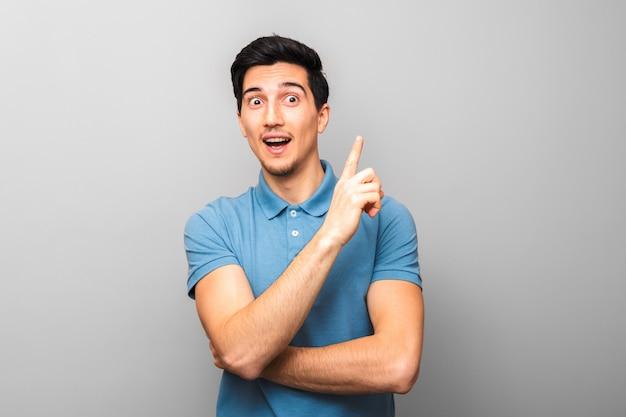 파란색 셔츠에 잘 생긴 남자는 그의 손가락으로 놀라운 아이디어 미소와 제스처를 얻었다. 회색 배경 스튜디오 촬영입니다.