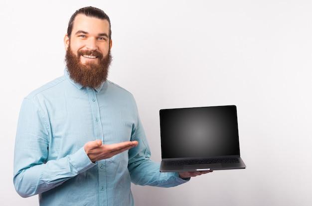 Красивый мужчина в повседневной синей рубашке показывает пустой экран на ноутбуке и улыбается над белой стеной