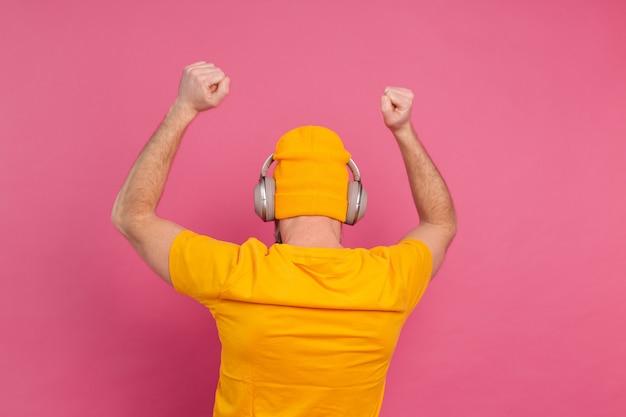 분홍색 배경에 고립 된 헤드폰으로 캐주얼 춤에 잘 생긴 남자