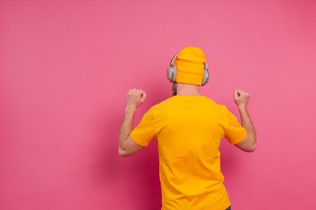 Красивый мужчина в случайных танцах с наушниками, изолированные на розовом фоне