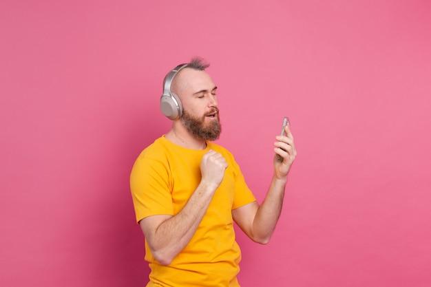 휴대 전화 및 분홍색 배경에 고립 된 헤드폰 캐주얼 춤에 잘 생긴 남자