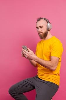ピンクの背景に分離されたヘッドフォンで音楽をカジュアルに聴いてハンサムな男