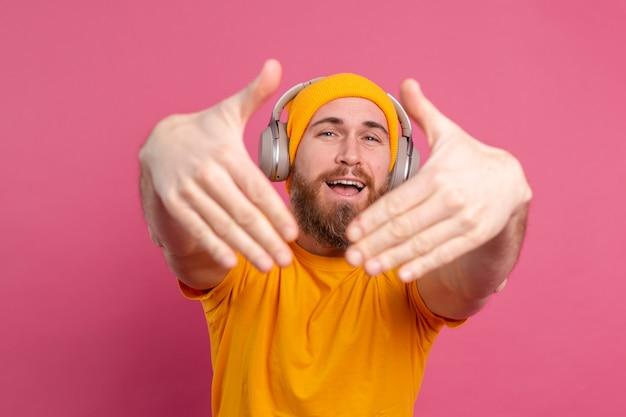 분홍색 배경에 고립 된 헤드폰으로 음악을 듣고 캐주얼에 잘 생긴 남자