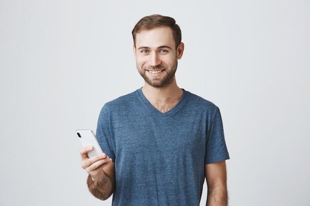 Красивый мужчина в повседневной футболке с помощью мобильного телефона