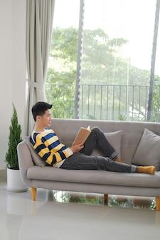 Красивый мужчина в повседневной одежде, улыбаясь, лежа на диване, читая портативную книгу.