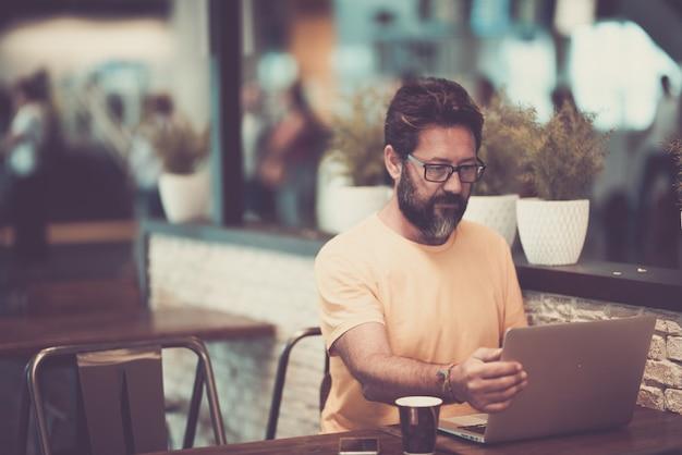 コーヒーショップでラップトップに取り組んでいる眼鏡のハンサムな男。レストランで携帯電話とコーヒーカップとテーブルの上のラップトップを使用して眼鏡の男。ノートパソコンを使用してインターネットを閲覧する男