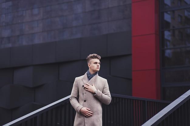 都市通りに立っている流行の服でハンサムな男