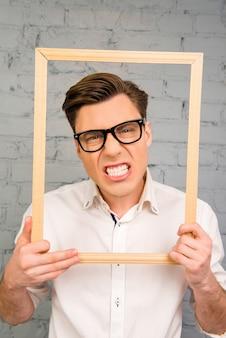 Красивый мужчина в очках, морщась и показывая зубы внутри кадра