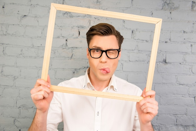 舌を見せて、フレームでウインクする眼鏡をかけたハンサムな男
