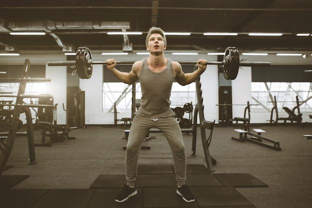 バーベルのジムトレーニングで筋肉と体調の良いハンサムな男