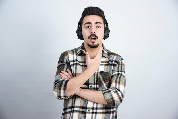 벽을 통해 음악을 듣고 헤드폰에 잘 생긴 남자.