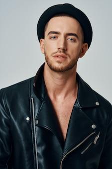 スタジオファッションのポーズをとる革のジャケットの帽子のハンサムな男。高品質の写真