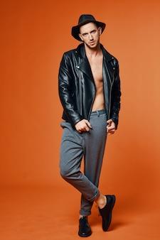 革のジャケットのハンサムな男は、胴体のファッションスタジオの孤立した背景をポンプアップ