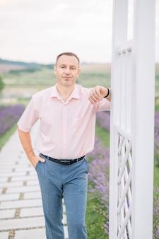 散歩を楽しんで、ラベンダー畑の背景に立って、白い木製のアーチに寄りかかって、薄手のシャツを着たハンサムな男。屋外の肖像画をクローズアップ