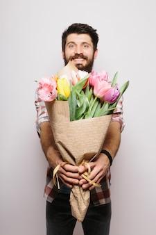 Красивый влюбленный мужчина, желающий счастливого дня святого валентина, дающий букет цветов на романтическое свидание, улыбаясь, в костюме над белой стеной