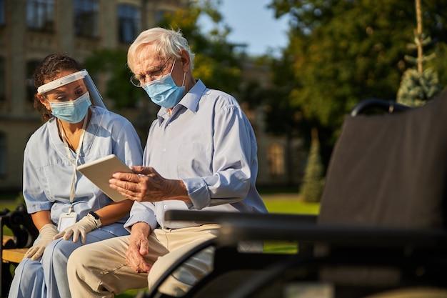 야외에서 성인 여성과 시간을 보내는 의학 마스크를 쓴 잘생긴 남자