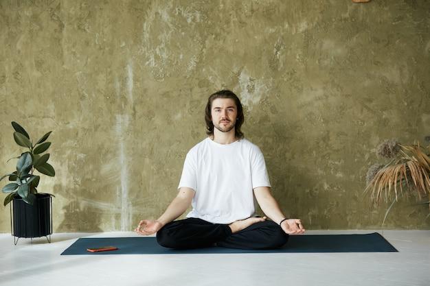 Красивый мужчина в позе медитации на коврике для йоги, парень в белой рубашке, держащий руки в мудре и улыбаясь в камеру, готовится к уроку йоги или медитации