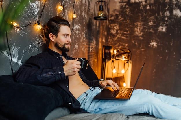 Красивый мужчина в утреннее время, лежа на кровати с таблеткой и чашкой кофе.