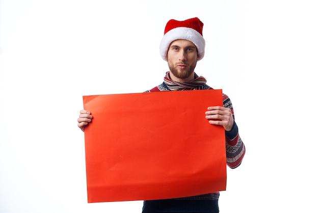 Красивый мужчина в новогодней одежде держит баннер праздник светлом фоне