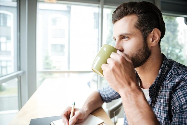Красивый мужчина в офисе коворкинг во время написания заметки, пить чай